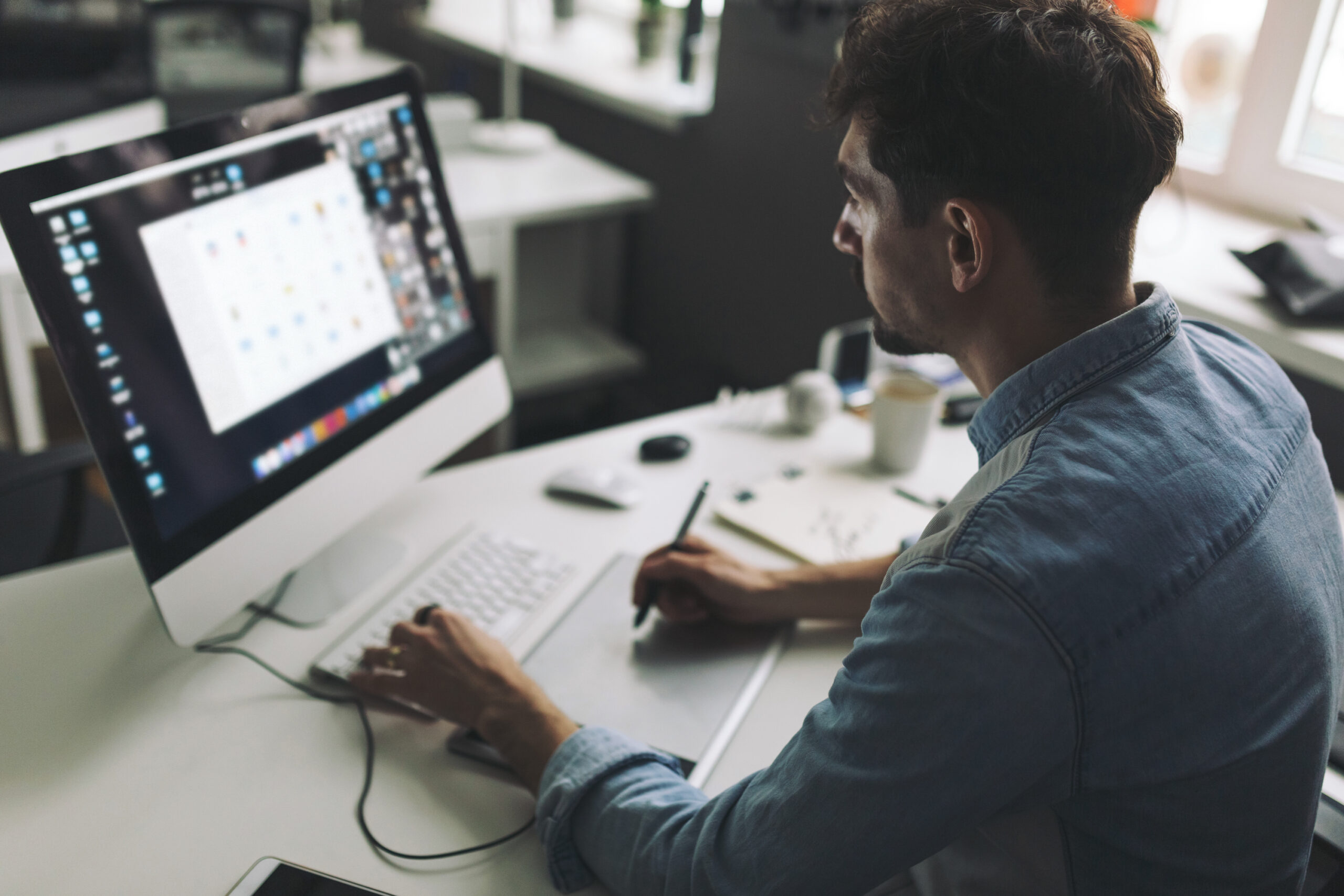 Modern designer sitting in front of computer and working in office